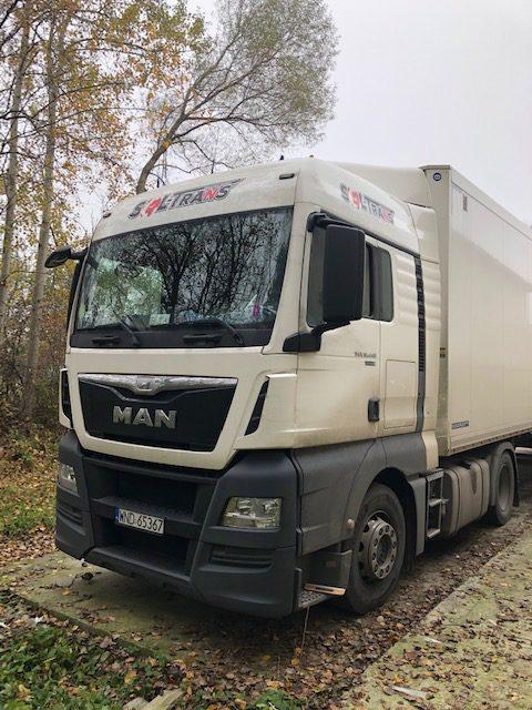 biała ciężarówka z naklejonym logiem firmy przewozowej