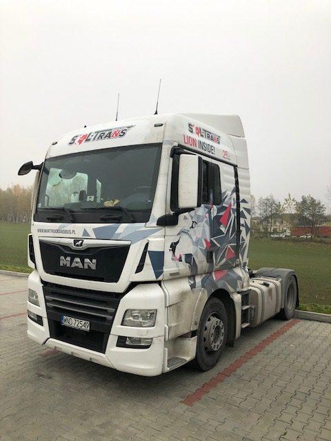 biała ciężarówka z oklejeniem