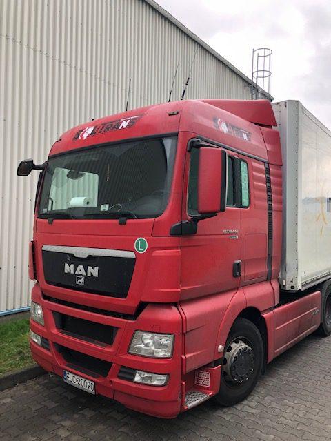 czerwony samochód ciężarowy z naklejonym logo firmy